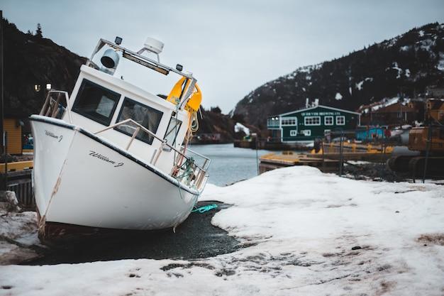 Biała i błękitna łódź na brzeg podczas dnia