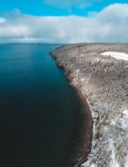 Biała i czarna formacja skalna w pobliżu błękitnego morza pod białymi chmurami w ciągu dnia