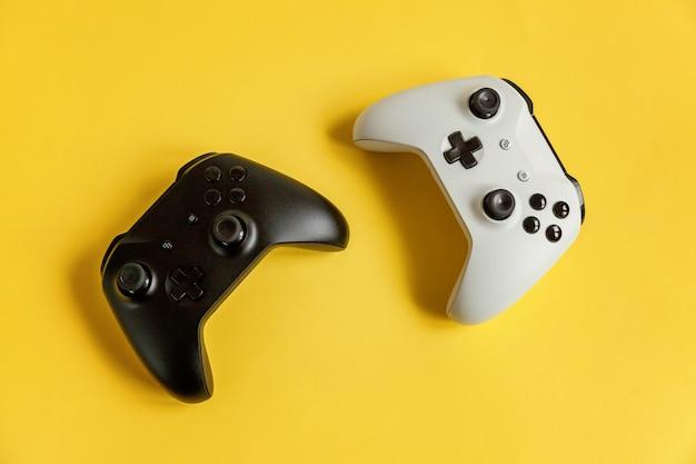 Biała i czarna konsola do gier z dwoma joystickami na żółtej, modnej, nowoczesnej, modnej powierzchni pin-up. koncepcja konfrontacji kontroli gier komputerowych. symbol cyberprzestrzeni