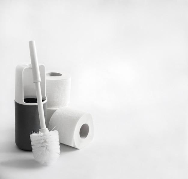 Biała i szara plastikowa szczotka toaletowa i papier toaletowy na białym tle. skopiuj miejsce