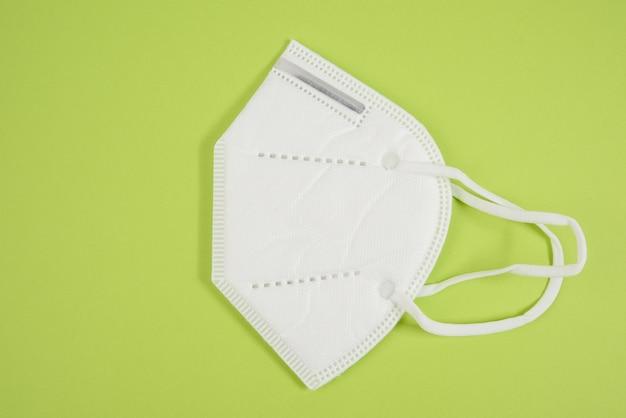 Biała jednorazowa maska medyczna na zielonej powierzchni, środki ochrony indywidualnej dróg oddechowych przed infekcjami wirusowymi, widok z góry