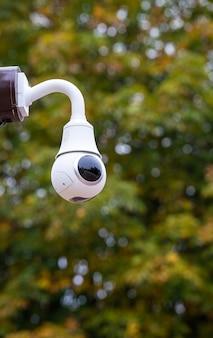 Biała kamera nadzoru bezpieczeństwa w parku.