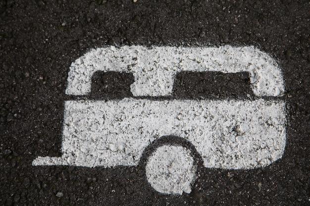 Biała karawana namalowana na asfalcie na miejscu parkingowym dla przyczep kempingowych
