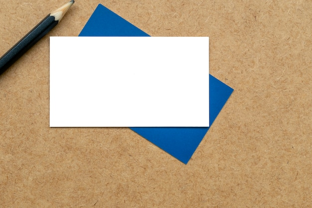 Biała karta na niebieskiej karcie i ołówku.