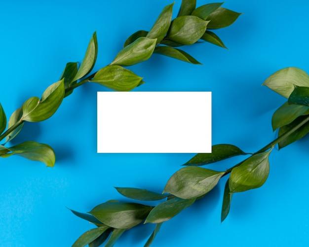 Biała karta papierowa uwaga jasne kwiaty kompozycja liść niebieskie tło makieta kartka z życzeniami kopia