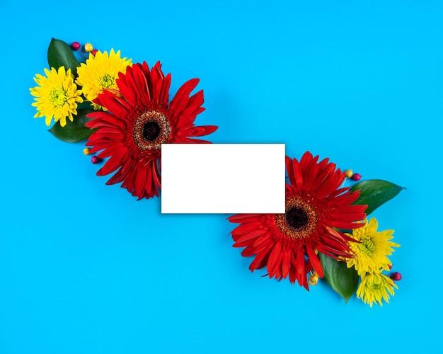 Biała karta papierowa uwaga jasne kwiaty kompozycja makieta kartkę z życzeniami kopia przestrzeń niebieskie tło