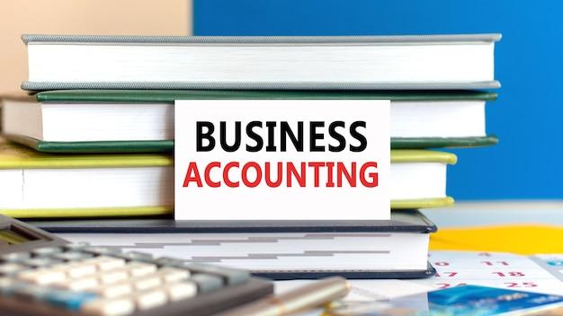 Biała karta z tekstem rachunkowości biznesowej stoi na biurku przed ułożonymi książkami, kalkulatorem, długopisem, kartą kredytową. koncepcja biznesowa i finansowa.