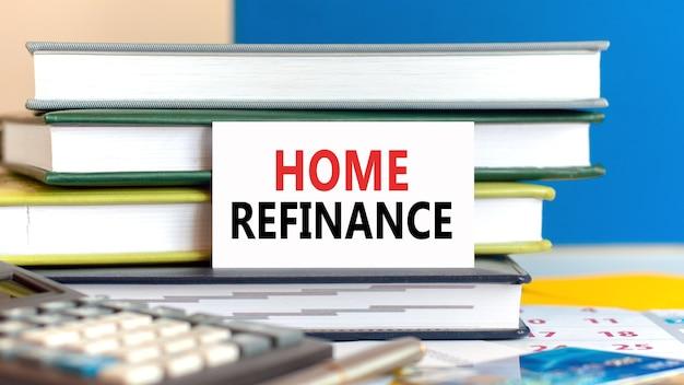 Biała karta z tekstem refinansowania domu stoi na biurku przed ułożonymi książkami, kalkulatorem, długopisem, kartą kredytową. koncepcja biznesowa i finansowa.