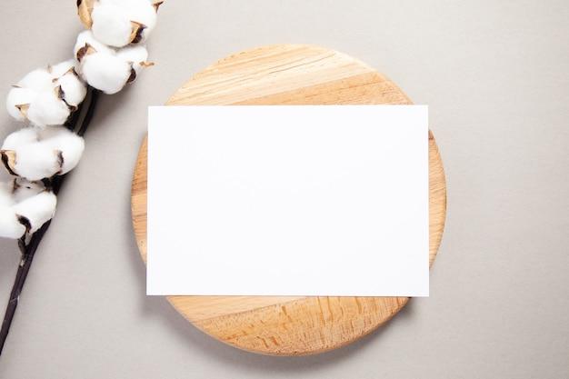 Biała karta zaproszenie na drewno z gałęzi bawełny