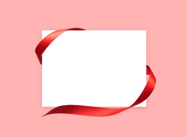 Biała kartka papierowa z czerwoną satynową tasiemką.