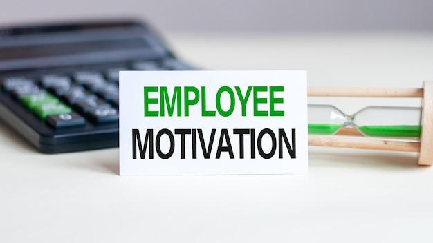 Biała kartka papierowa z napisem motywacja pracownika, kalkulator i klepsydra z tyłu