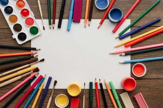 Biała kartka papieru a4 leży na drewnianej brązowej ramie stołu obok farb, pędzli, kolorowych ołówków.