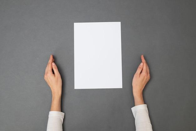 Biała kartka papieru do tekstu. kobieta trzyma pusty arkusz papieru na szarej teksturze. widok z góry