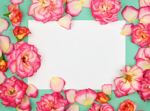 Biała kartka papieru i pąki różowych róż