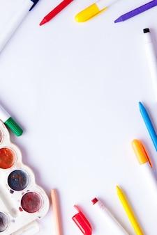 Biała kartka papieru leżała na drewnianym stole obok ołówków, farb i markerów. powrót do szkoły. przybory szkolne i biurowe. edukacja i szkoły granicy pojęcie i kopii przestrzeń na drewnianym tle