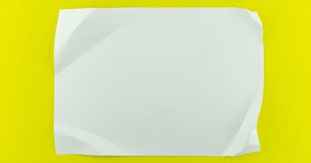 Biała kartka papieru na żółtym tle papieru miejsce na reklamę tekstową.