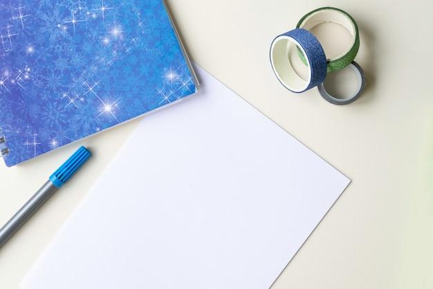 Biała kartka papieru, niebieska nuta z płatkami śniegu, flamastr i błyszcząca, wielokolorowa dekoracyjna taśma klejąca. pojęcie koncentracji, zimy i planów na następny rok.