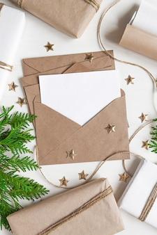 Biała kartka papieru w kraftowej kopercie na blacie stołu jest pusta na kartkę świąteczną