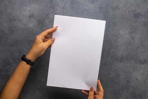 Biała kartka papieru w rękach kobiet