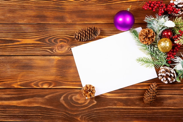 Biała kartka świąteczna i ozdoby świąteczne na drewnianym stole, leżał na płasko