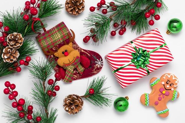 Biała kartka świąteczna z ludzikiem z piernika i skarpetą ozdobioną filcowym reniferem. ciasteczka i dekoracje wykonane z zielonych gałęzi świerkowych i czerwonych jagód ostrokrzewu.