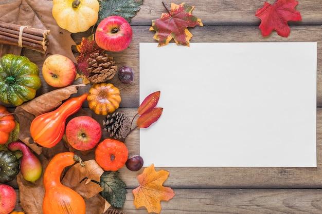 Biała kartka w pobliżu liści i warzyw