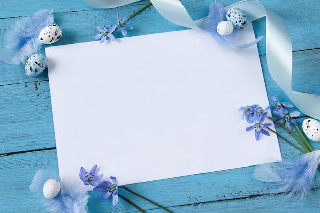 Biała kartka wielkanocna, kwiaty przebiśnieg, pisanki i pióra na niebieskiej desce.