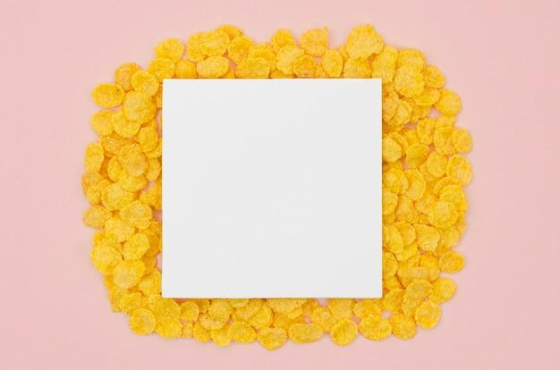 Biała kartka z miejsca kopiowania otoczonego płatkami kukurydzy