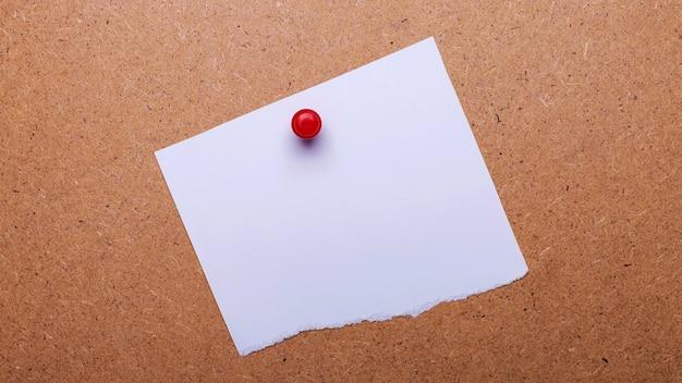 Biała kartka z miejscem na wstawienie tekstu lub ilustracji przypinana jest do drewnianego tła za pomocą czerwonego guzika. szablon