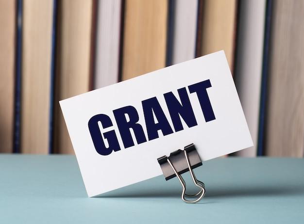 Biała kartka z napisem grant stoi na spinaczu do referatów na stole na tle książek. rozogniskowanie