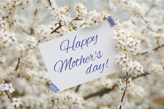 Biała kartka z napisem happy mother's day na stole z białych kwiatów wiśni