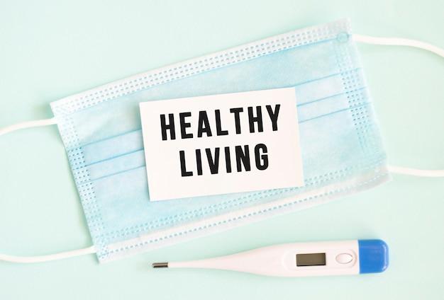 Biała kartka z napisem zdrowe życie na medycznej masce ochronnej.
