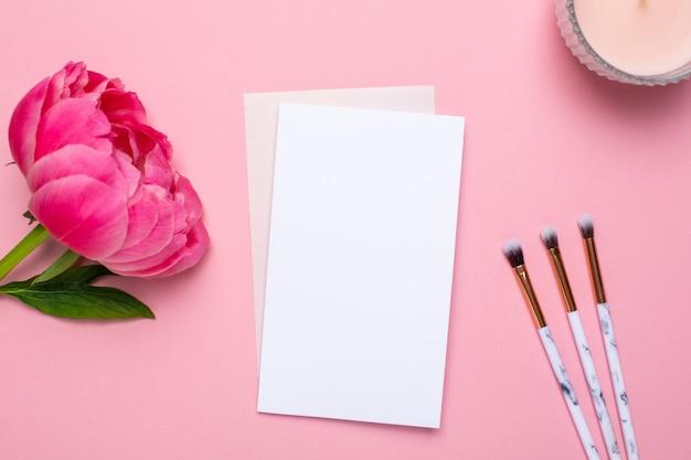 Biała kartka z pędzlami do makijażu i piękną piwonią z kwiatów