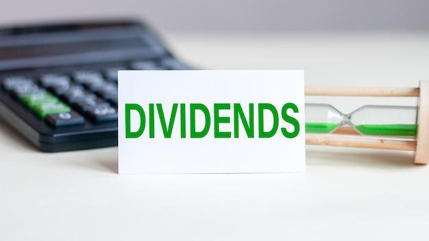 Biała kartka z tekstem dividends, kalkulator i klepsydra w tyle