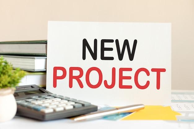 Biała kartka z tekstem nowy projekt stoi na biurku przed ułożonymi książkami, kalkulatorem, długopisem, zieloną rośliną doniczkową. koncepcja biznesowa i finansowa. selektywna ostrość.