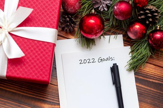 Biała kartka z tytułem goli 2022 i czarnym markerem na drewnianym stole dekoracje sylwestrowe