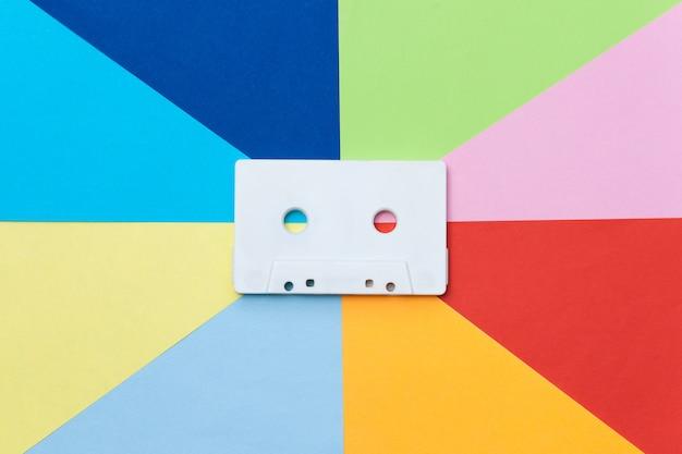 Biała kaseta z taśmą retro na wielokolorowym tle, koncepcja kreatywna.