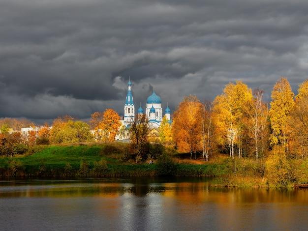 Biała katedra w oddali otoczona złotymi jesiennymi drzewami. stare miasto gatczyna.