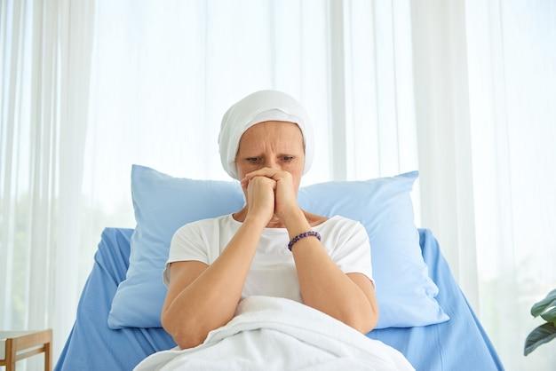 Biała kaukaska kobieta bez włosów i brwi czuje się źle modli się i czeka na chemioterapię w sali szpitalnej, koncepcja miesiąca świadomości raka piersi.