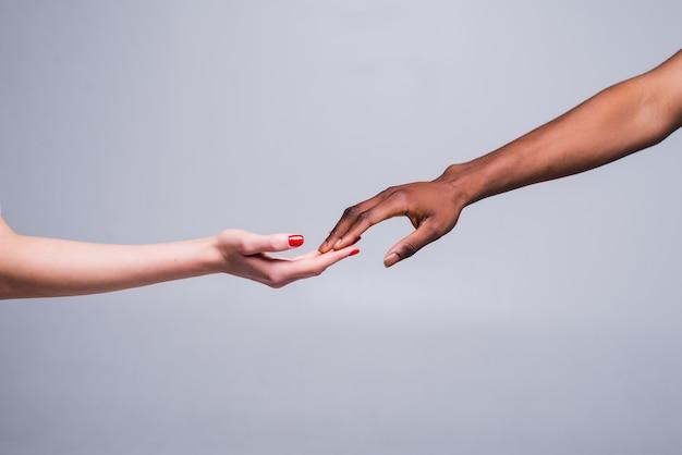 Biała kaukaska ręka żeńska i czarna męska ręka trzymająca palce razem