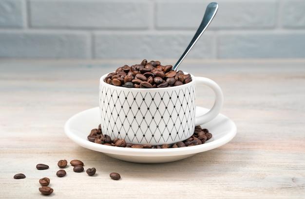 Biała kawa puchar pełen ziaren kawy i łyżką. widok z boku, z miejscem na kopiowanie.