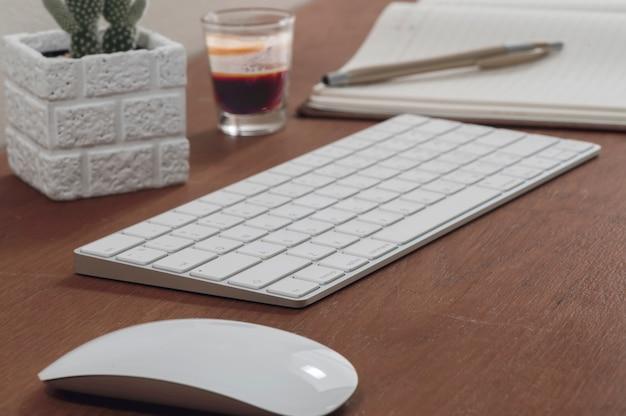Biała klawiatura i mysz komputerowa z rośliny doniczkowej, szklanka gorącej kawy na drewnianym stole.