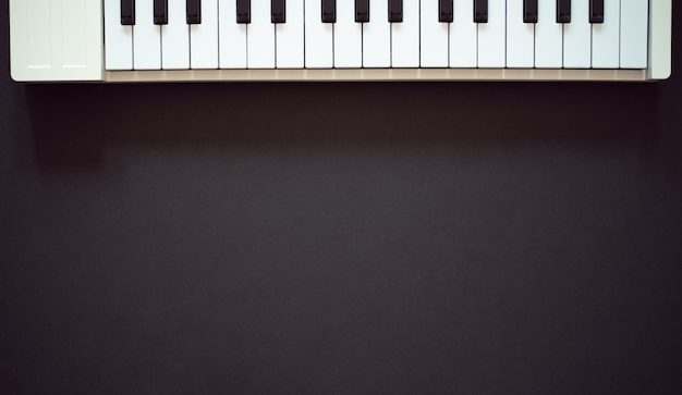 Biała klawiatura midi na ciemnym tle płaski widok z góry