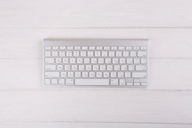 Biała klawiatura na drewnianym stole