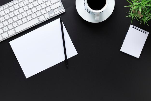 Biała klawiatura; papier; ołówek; filiżanka kawy; spirala notatnik i roślina doniczkowa na czarnym tle