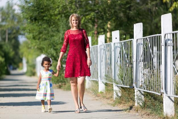 Biała kobieta idzie ulicą z czarną dziewczyną.