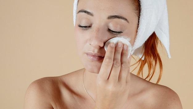 Biała kobieta otrzymuje oczyszczający krem do twarzy