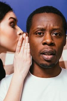 Biała kobieta szepcząca do ucha do czarnego mężczyzny, zbliżenie