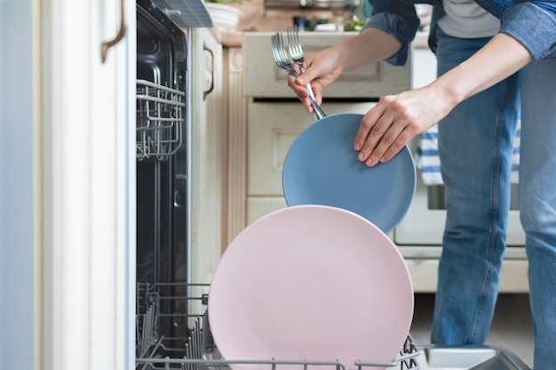 Biała kobieta zmywa naczynia ręcznie lub wkłada je do zmywarki do mycia kobiet w pracach domowych house