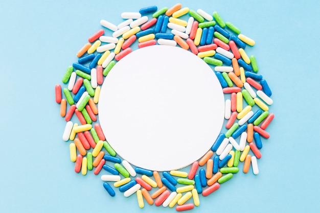 Biała kółkowa puste rama dekorująca z kolorowymi cukierkami na błękitnym tle